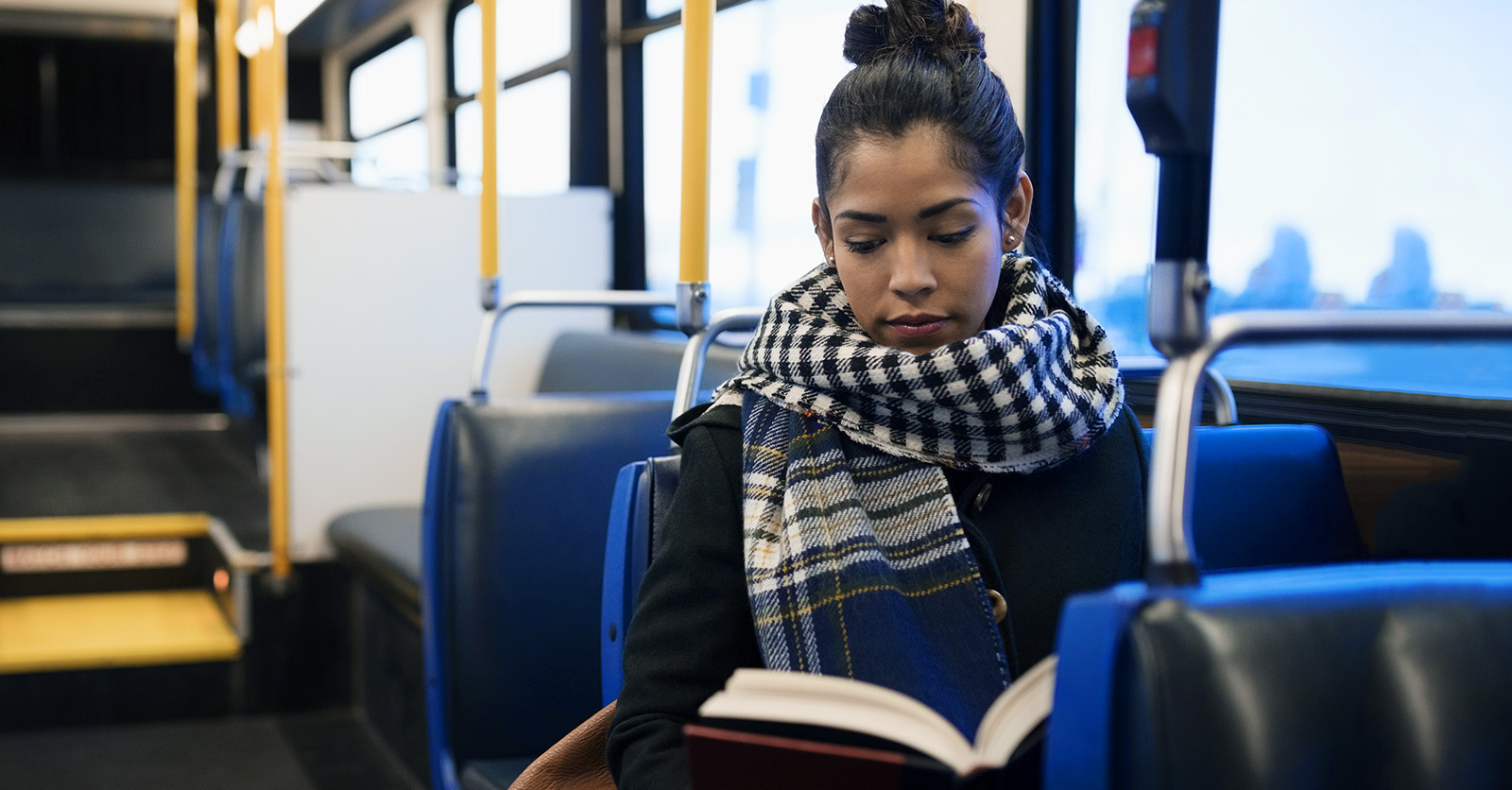 Female student on bus studying with a book