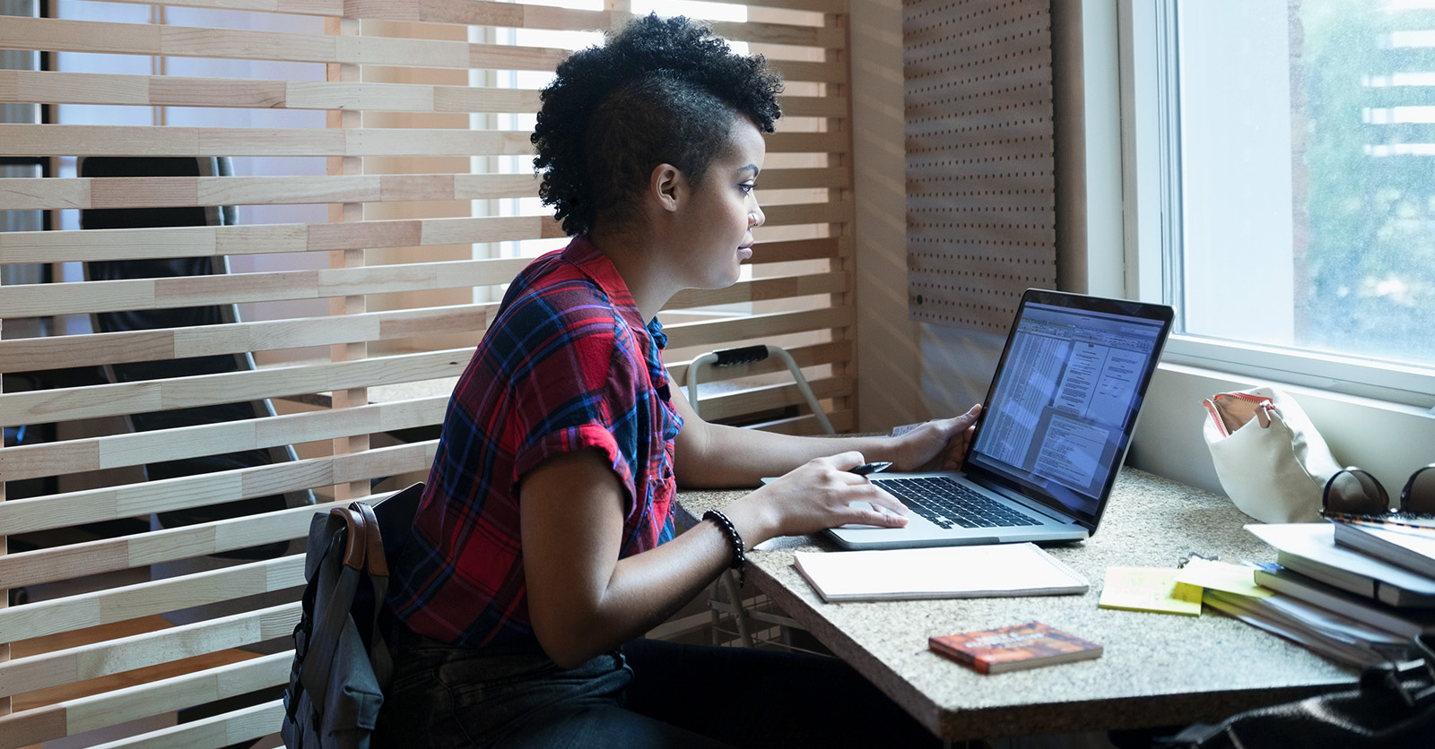 Creative businesswoman using laptop at window in office